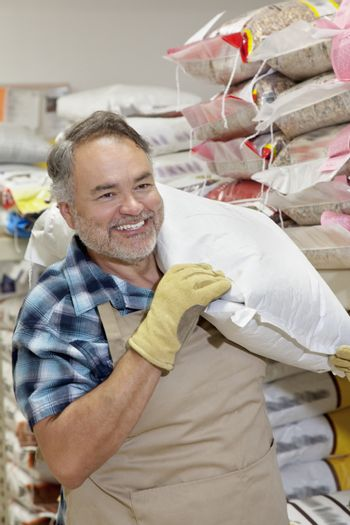 Happy mature salesperson carrying sack in feed store