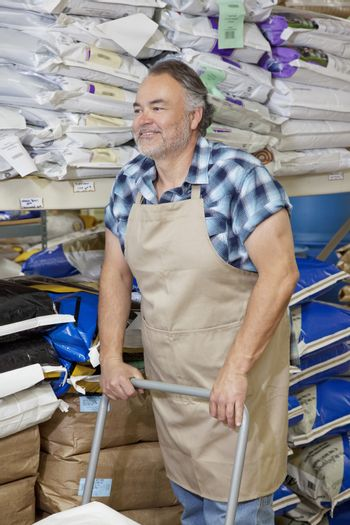 Happy mature man pushing cart in feed store