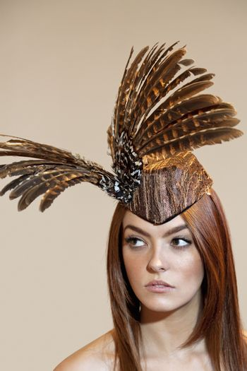 Young woman with feathered headgear looking away over colored background