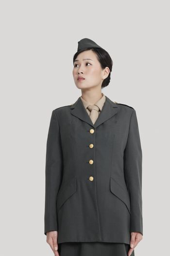 Female US military officer standing in attention as she looks away over gray background