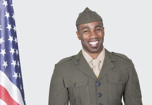 Portrait of a male US soldier smiling with American flag over gray background