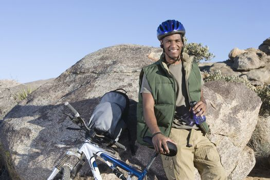 Portrait of an African American man leaning against rock with mountain bike