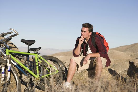 Thoughtful man sitting with mountain bike on rock against clear blue sky