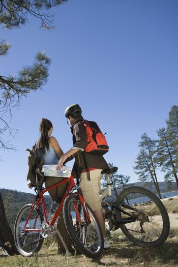 Rear view of a young couple standing with mountain bikes in recreation area