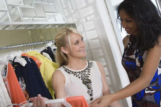 Shop assistant helps woman with dress