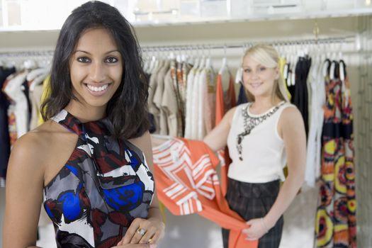 Shop assistant holds dress for customer