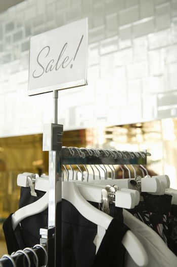 """Clothes hanging on a rack in fashion retail store with """"SALE"""" sign on the plate"""
