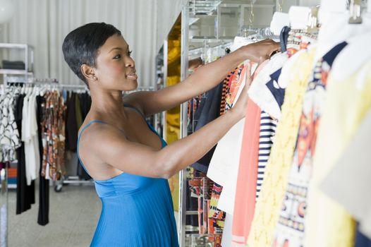 Woman looks through clothes rail