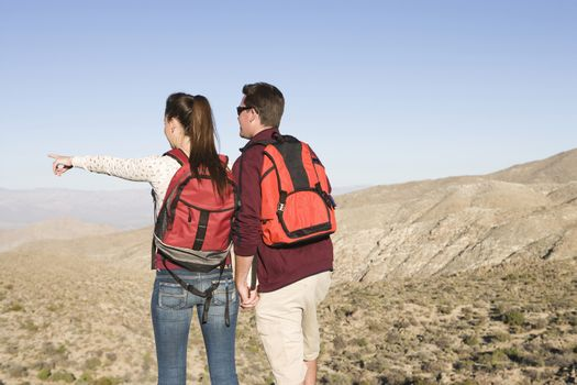 Rear view of a couple with backpacks looking at view while standing in an arid landscape
