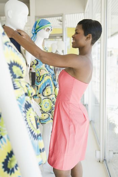 Shop assistant makes adjustment to mannequin