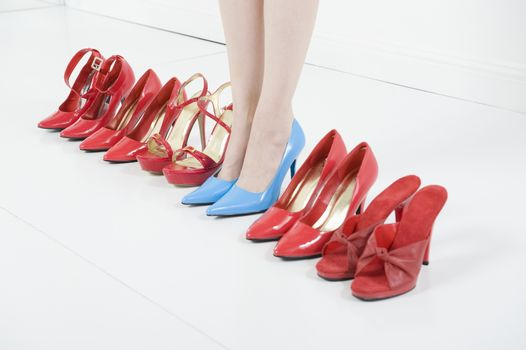 Line of red shoes with a woman standing in blue shoes