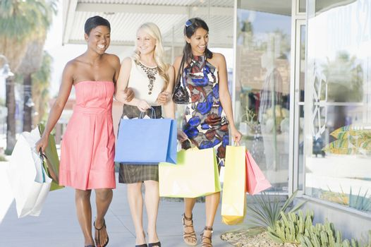 Three friends walk side by side in shopping mall