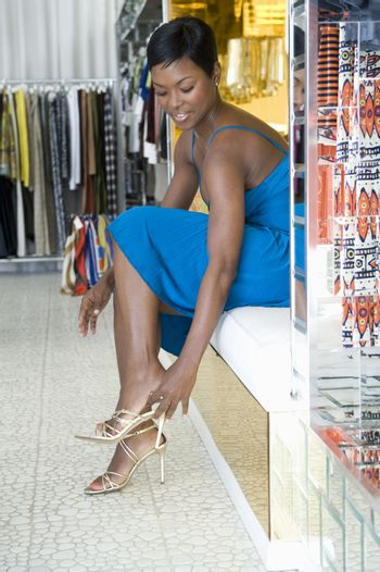 Woman tries on gold high heeled sandals