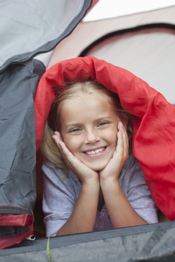 Girl under sleeping bag smiles from tent