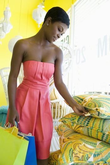 African American woman looking at price tag on cushions at home decor store