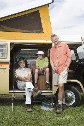 Father son and grandson in campervan prepare to go fishing