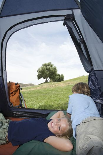 Brother and sister lie in a tent