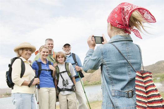 Girl in bandana photographing family on activity holiday