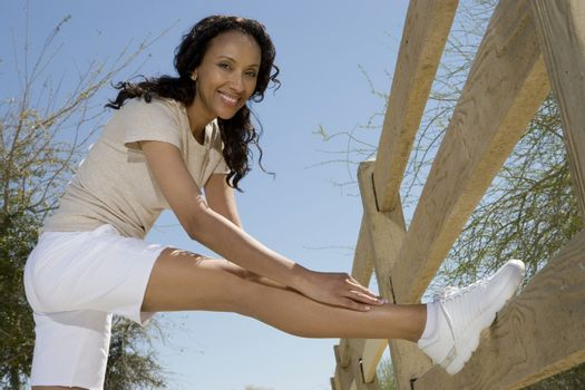 Mid adult woman stretches hamstring against fence