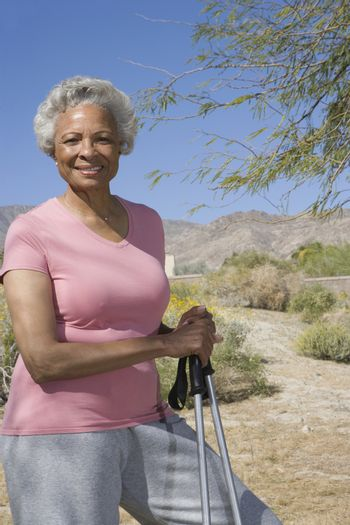 Senior woman stands with walking poles