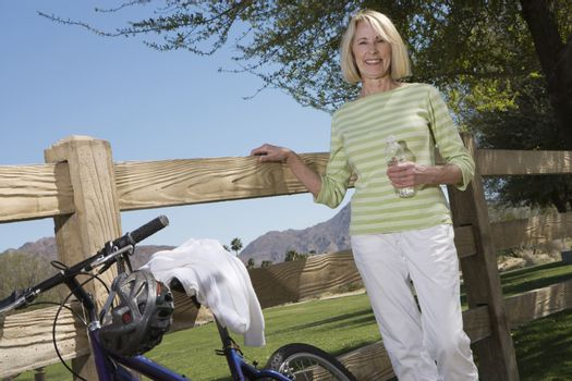 Mature woman stands with mountain bike at fence