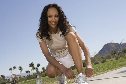 Mid adult woman ties shoelaces