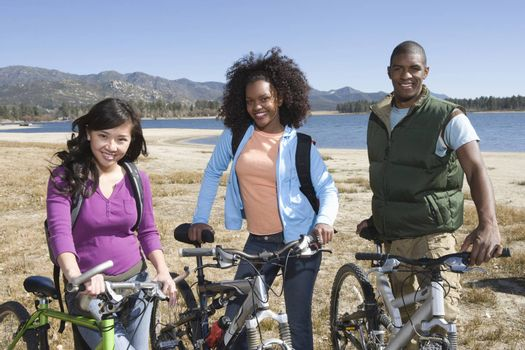 Multiethnic Friends With Mountain Bikes By The Lake