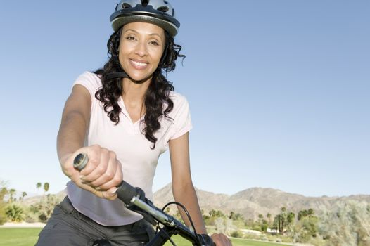 Woman in cycling helmet holds handlebars of mountainbike