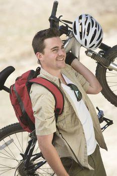 Man carrying mountain bike as he looks away