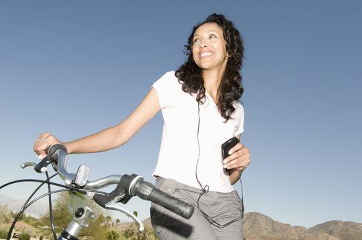 Mid adult woman listens to MP3 holding handlebars on mountainbike