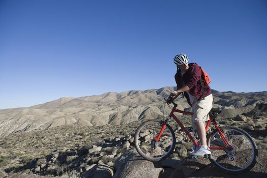 Full length of man with mountain bike in an arid landscape looking back his over shoulder