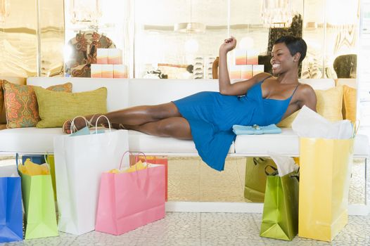 Woman lies with shoppig bags in store seating area