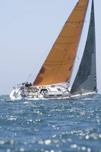 Yacht with yellow sail competes in team sailing event California