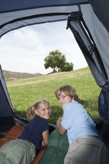 Brother and sister lie in a tent looking back over their shoulders