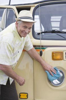 Senior man polishes the headlights on his campervan