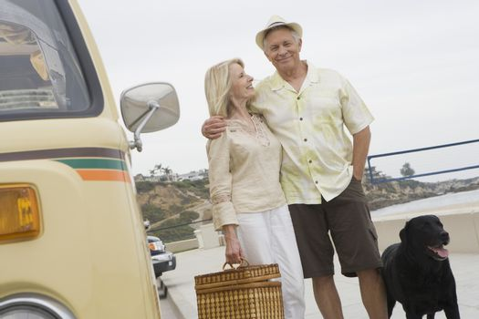 Senior couple stand on beach promenade with campervan