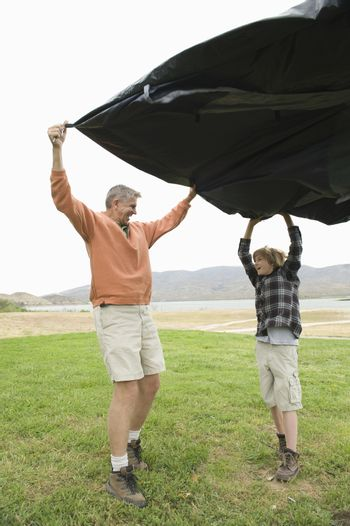 Father and son hold groundsheet in wind