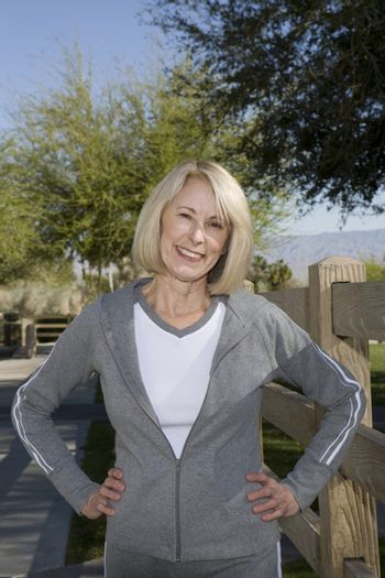 Mature adult woman stands smiling in tracksuit with hands on hips