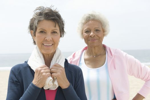 Two senior women stand on coastal promenade