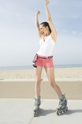 Woman on in-line skates with arms raised in joy