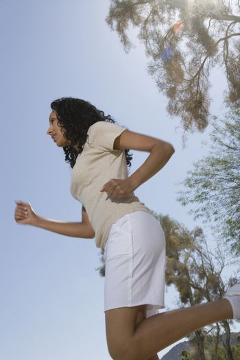 Mid adult woman jogging sideview