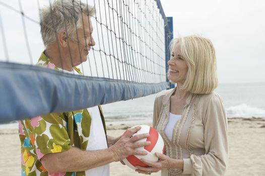 Senior couple stand at volleyball net