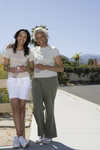 Mother and daughter stand on pavement in sportswear