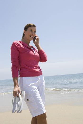 Woman on mobile phone on beach