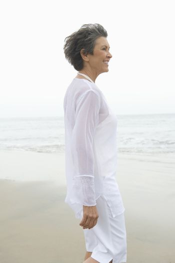 Mature woman in white clothing at waters edge