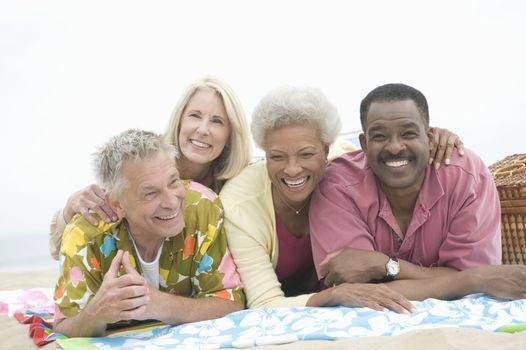 Four senior friends lie on their stomachs on the beach