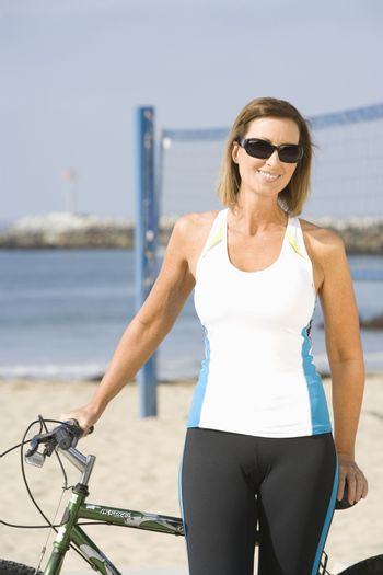 Sporty woman at the beach with bike