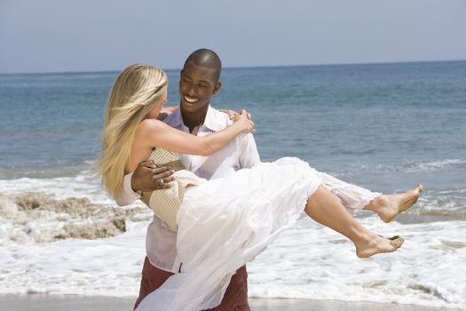Man carrying woman on beach