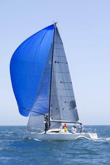 Yacht with blue sail competes in team sailing event California