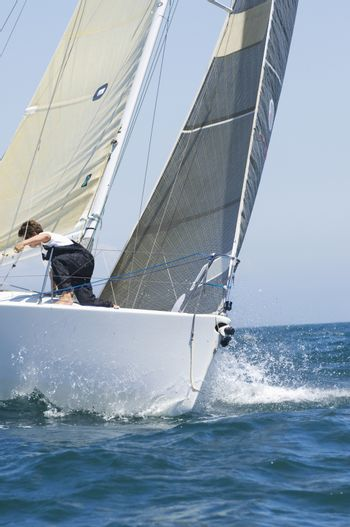 Crew member on board yacht competing in team sailing event California